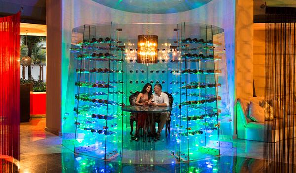 Couple dégustant un souper dans une cave à vin illuminée