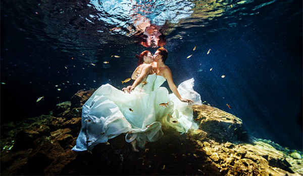 Two brides kissing underwater