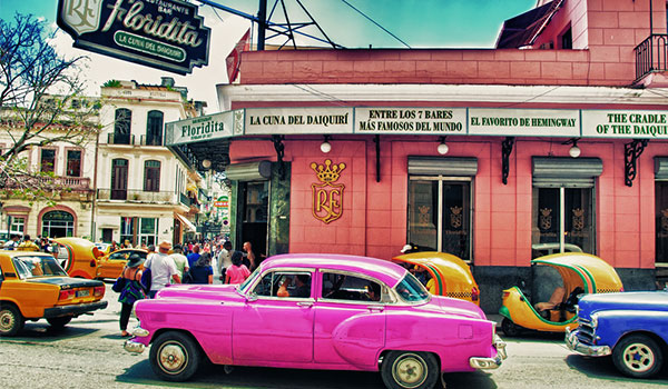 Pink vintage car driving down the streets of Havana