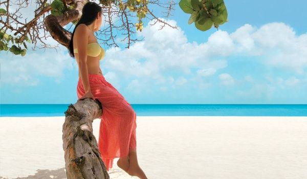 Woman sitting on tree overlooking beach