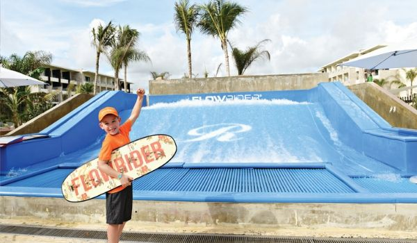 Young boy standing with surf board in front of FlowRider