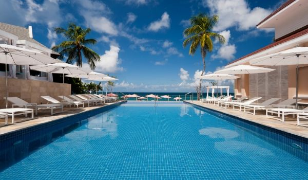 Sparkling pool lined with white lounge chairs and umbrellas
