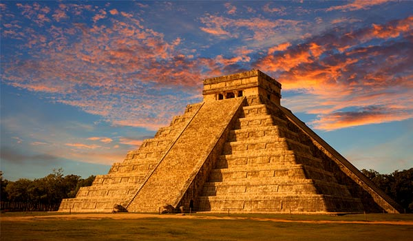 View of Mayan pyramid from the ground at sunset