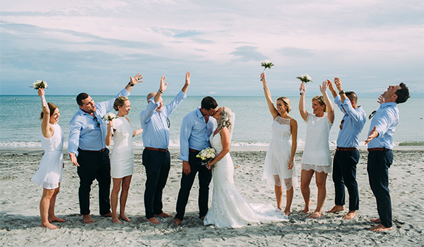 Bride and groom kissing on the beach next to their groomsmen and bridesmaids