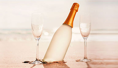 Sparkling wine and fluted glasses on a sandy beach