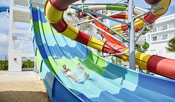 Two people sliding down a water slide