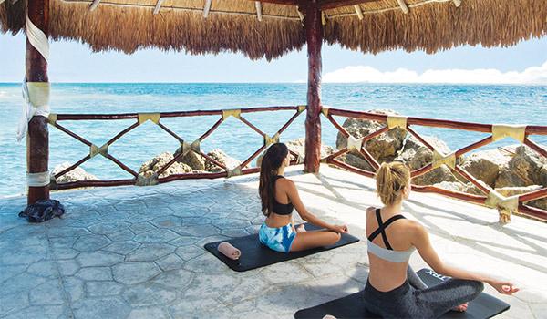 Deux femmes faisant du yoga dans un pavillon face à la mer