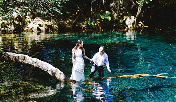 Bride and groom standing in the waters of a lagoon