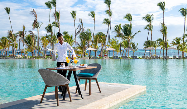Waiter pouring mimosas at a breakfast table in the middle of the pool
