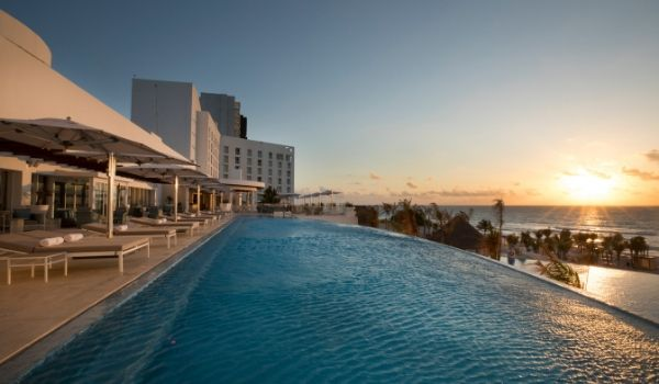 Infinity pool overlooking white-sand beach at sunset