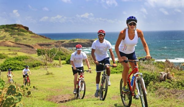 People biking up a lush hillside overlooking the coast