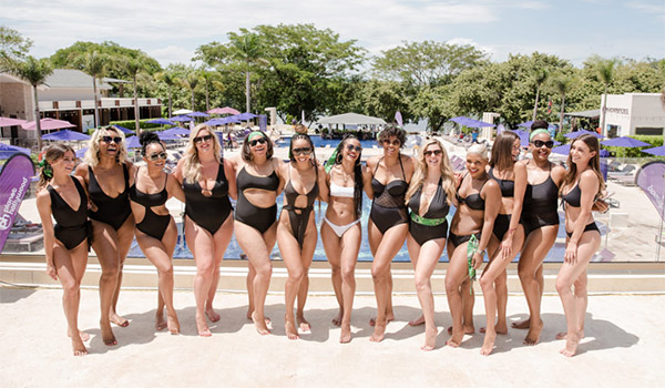 Group of women wearing swimsuits standing by the pool