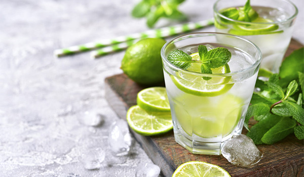 Two Mojitos garnished with fresh mint and lime wheels
