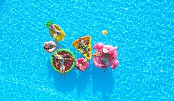 Birds' eye view of people lounging in the pool on pool floaties