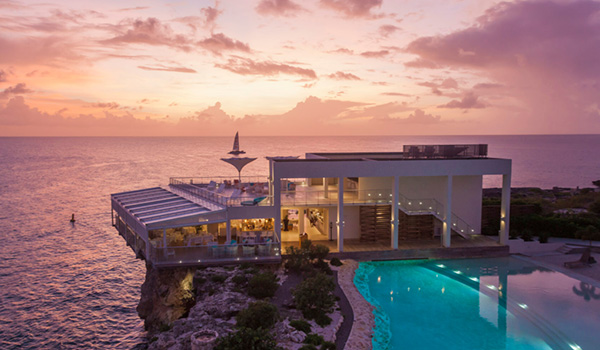 Restaurant perched on a cliffside overlooking the ocean with a pool
