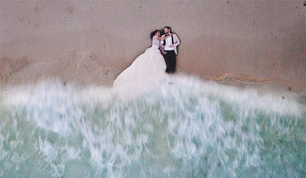 Aerial view of bride and groom lying on the beach