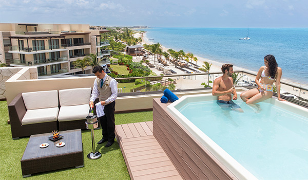 Couple sitting in a rooftop Jacuzzi overlooking the ocean while butler pours them champagne