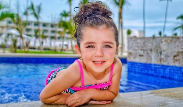 Young girl hanging out by sparkling pool