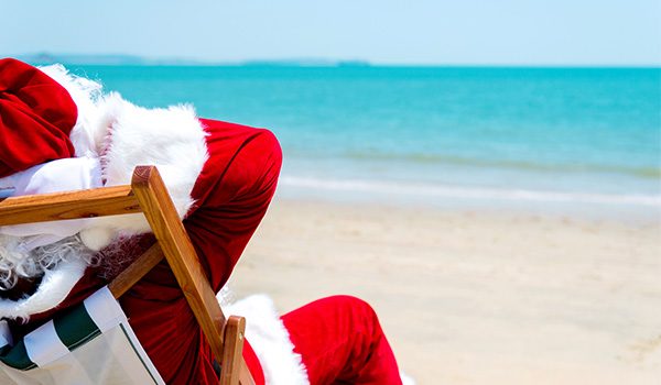 Santa Claus resting on a beach chair overlooking the ocean