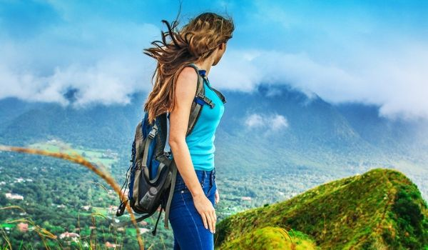 Woman wearing a backpack overlooking lush landscapes