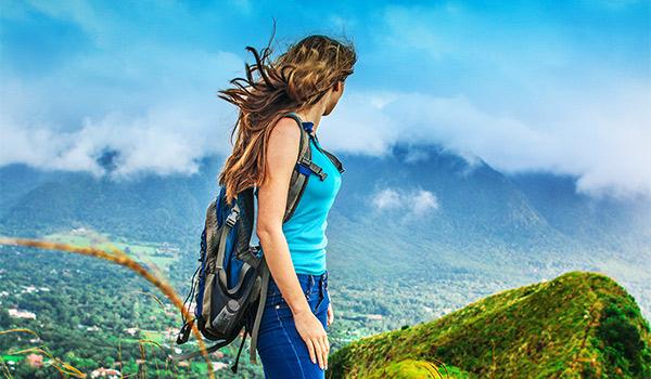 Femme portant un sac à dos regardant des paysages luxuriants à ses pieds