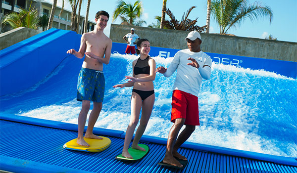 Instructor teaching children how to ride the FlowRider