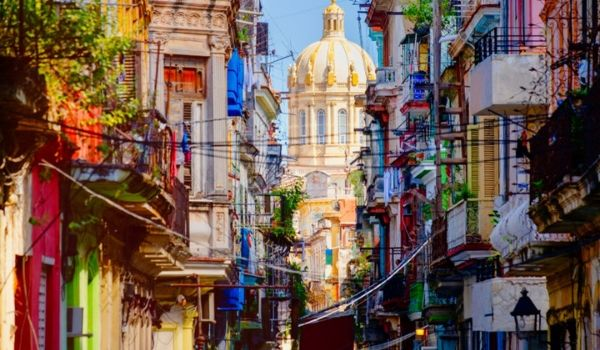 Street lined with colonial buildings overlooking an ornate church in Havana