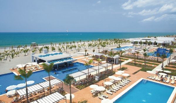 Riu Playa Blanca pool complex and swim-up bar overlooking the beach lined with palm trees.