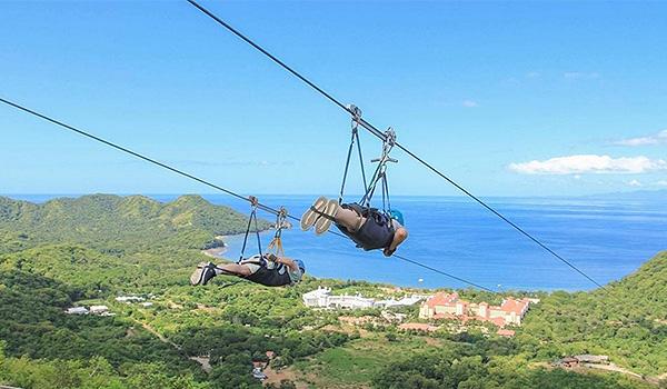 Two people Superman ziplining overlooking the coast