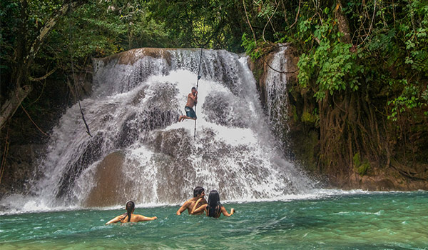 Person swinging on a rope over a waterfall into the natural pool below