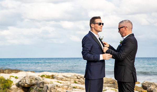 Colin adjusting Justin's bowtie on the beach