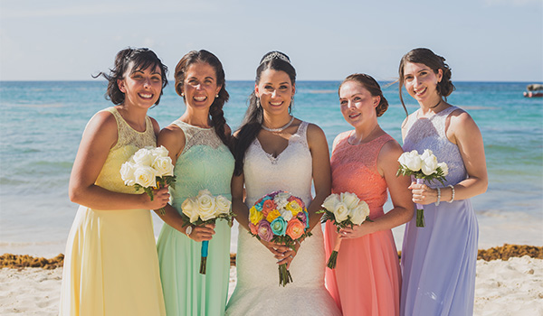 Ana and her bridesmaids posing in front of the sparkling ocean
