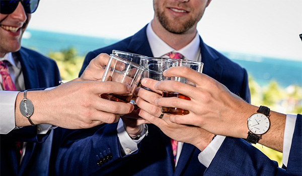 Men holding whiskey glasses standing on a balcony overlooking the ocean