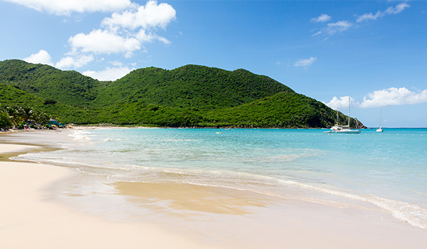 Crystal-clear waters fringed by a white-sand beach with lush mountains in the background