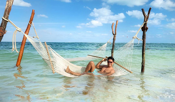 Man lounging on an overwater hammock
