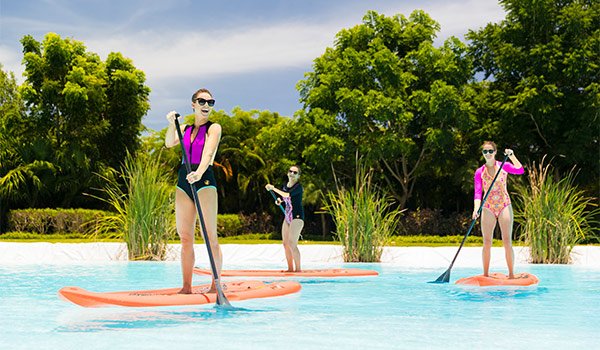 Three women paddle boarding across a pool