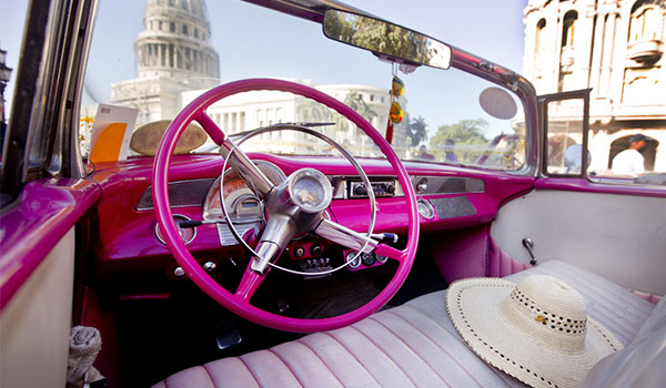 Inside a classic American car with Havana's historic buildings in the background