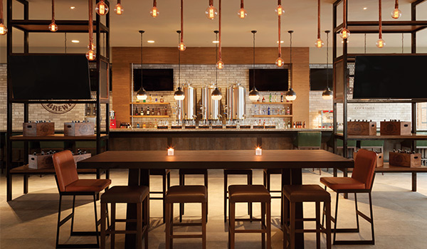 Trendy bar area with string lights, beer taps and a rectangular table with chairs.
