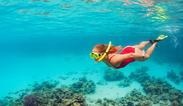 Jeune femme faisant de la plongée avec tuba avec une étoile de mer