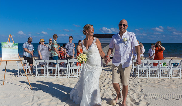 Bride and groom walking down the aisle on the beach