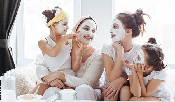 Femme et trois jeunes filles profitant d'un soin du visage