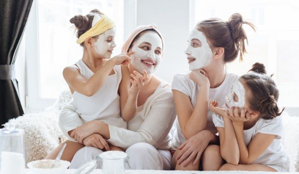 Woman and three young girls enjoying face mask treatment