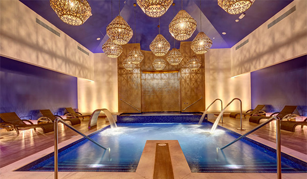 Spa with a sprawling Jacuzzi surrounded by loung chairs