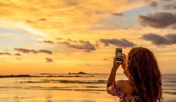 Woman taking a picture of tropical sunset