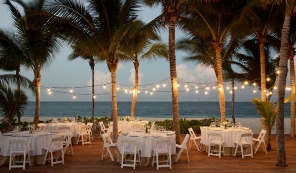 Dinner tables by the beach under twinkling lights and palm trees
