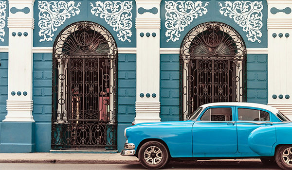 Classic blue car driving beside a uniquely-decorated wall