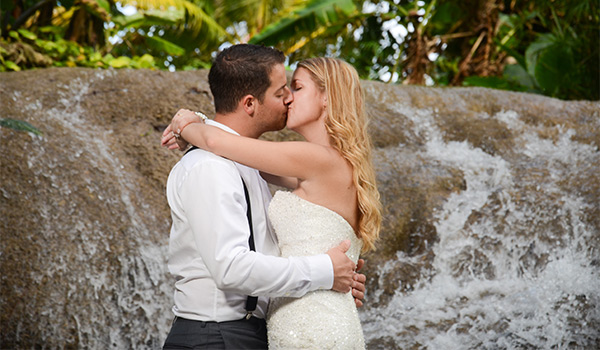 Bride and groom kissing by a waterfall