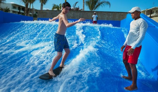 Man teaching a boy how to surf on the FlowRider