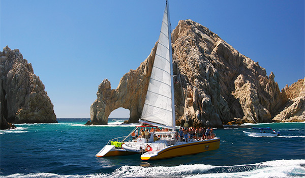 Catamaran sailing by the famous arch of Los Cabos