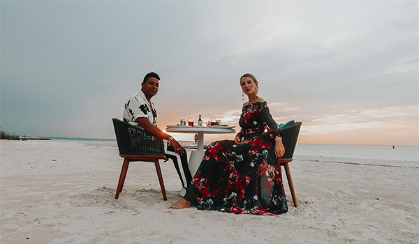 Man and woman sitting at a table on a secluded beach